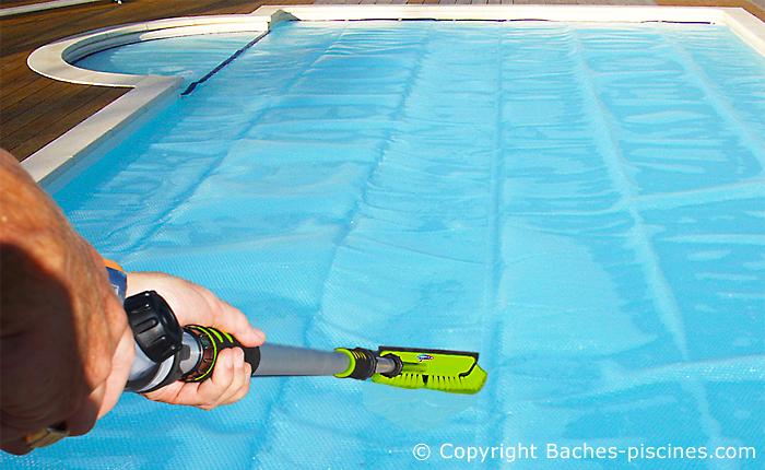 Brosse avec jet d'eau pour nettoyer une bâche piscine